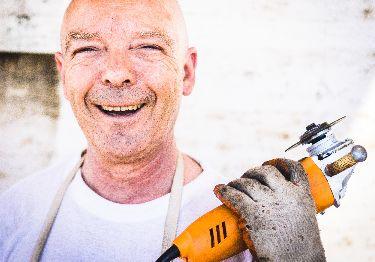 Trabajador sonriente junto con su herramienta de trabajo