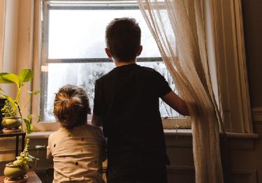 Dos menores miran por la ventana